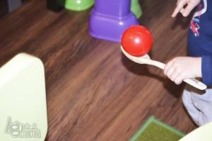 drewniana łyżka z czerwoną piłką
